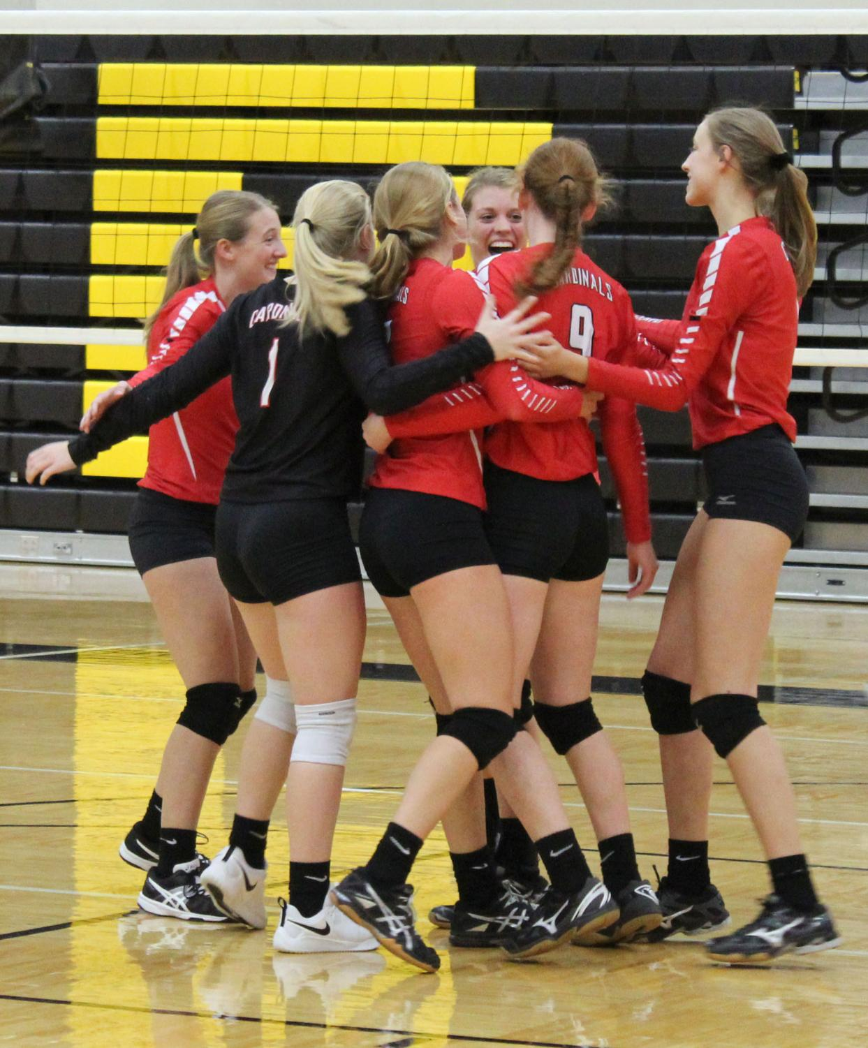 "The team celebrates a point by gathering together in the middle of the court.  ""I felt like we did well despite losing, but we could have talked more. If we had we might have done better"" Senior Kayla Koester said."