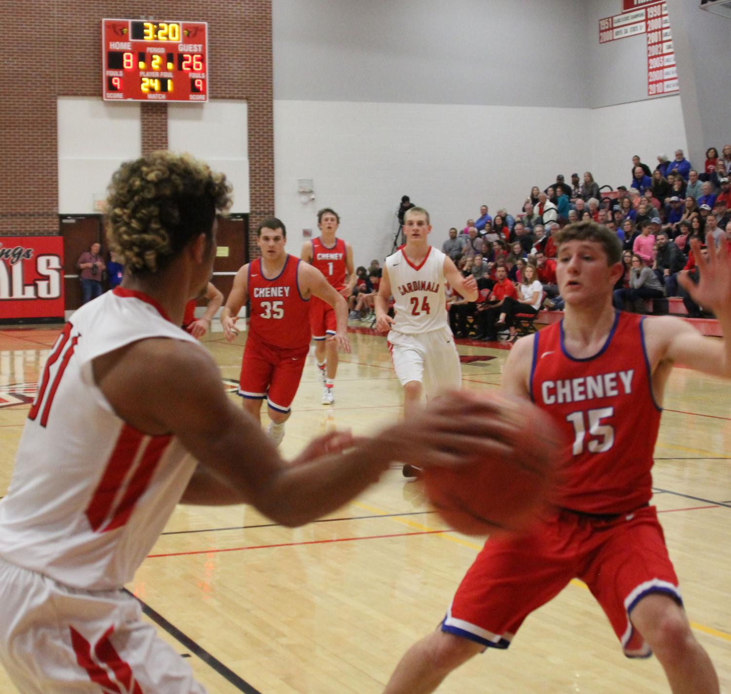 Sophomore Jonathan Wright passes the ball across the baseline during the Cheney game. The boys fought hard but lost 55-33.