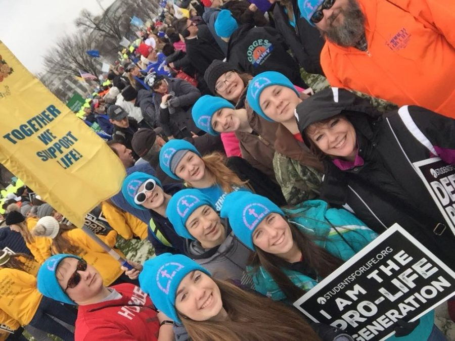 The+March+for+Life+group+gather+together+during+the+march+for+a+group+photo.+The+Conway+students+are+in+blue+hats+with+Becky+Heimerman+in+a+black+coat+next+to+them.+