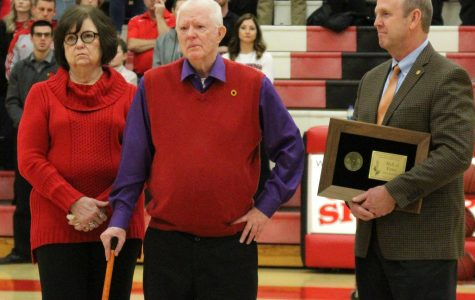 Between the girls and boys varsity game against Douglass, Fred Cottrell stands with his wife Janie as he is awarded with the KSHSAA Hall of Fame.