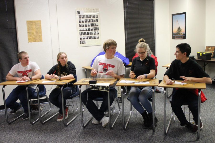 At League Scholars Bowl, team members senior Cooper Boyles, sophomore Lucy Boyles, senior Nathan Ohl, sophomore Sadie Schmanke, and junior Neal Zoglmann discuss a question.