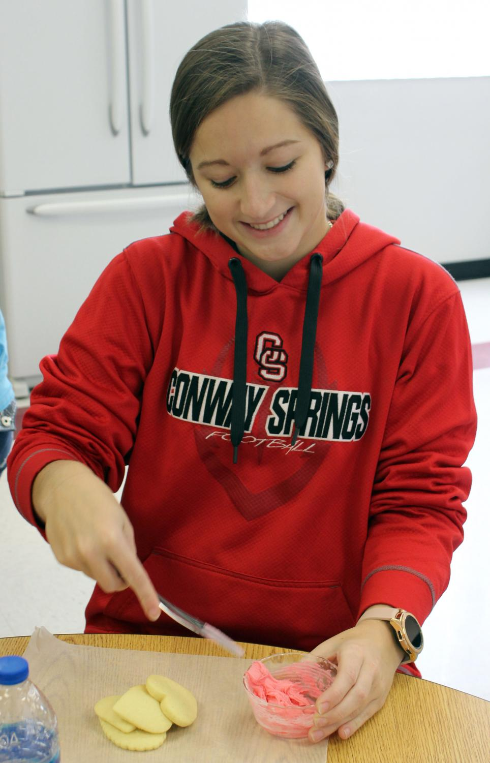For the Valentine's giveaway, senior Lesie Mies decorates heart-shaped cookies. This giveaway was hosted by the FCCLA group during FCCLA week.