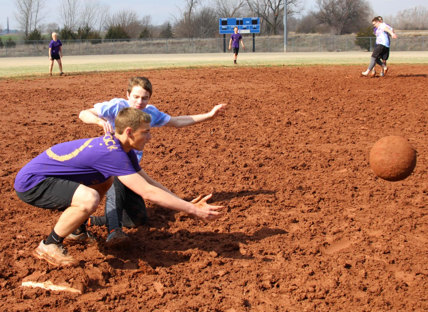 During kickball on March 23, junior Carson Clum slides into third base, making it safe, while junior Jack Ebenkamp waits for the ball. Carson's team was called Life's a Pitch, and they took fifth overall. Photo by Lexi Fisher.