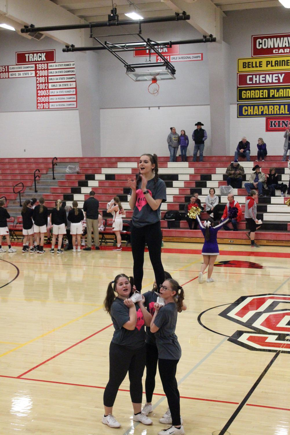 "In the 2018-2019 season, sophomore JoEllen Reep and junior Cierra Hiser base junior Jaylee Meyer as they do a cheer to get the crowd pumped. ""I'm really excited for this year because it's my senior year. I like stunts because you never know what's going to happen,"" Meyer said."
