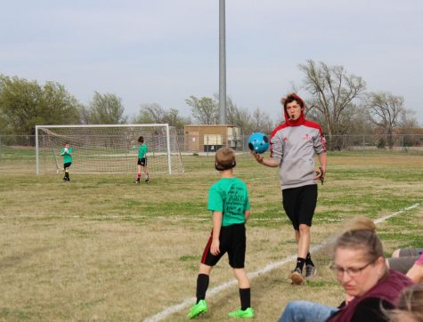 During a soccer game, Carter Bartonek hands the ball to a player to throw in bounds. This was the third day of games for the soccer season, and Bartonek had reffed six games by now.