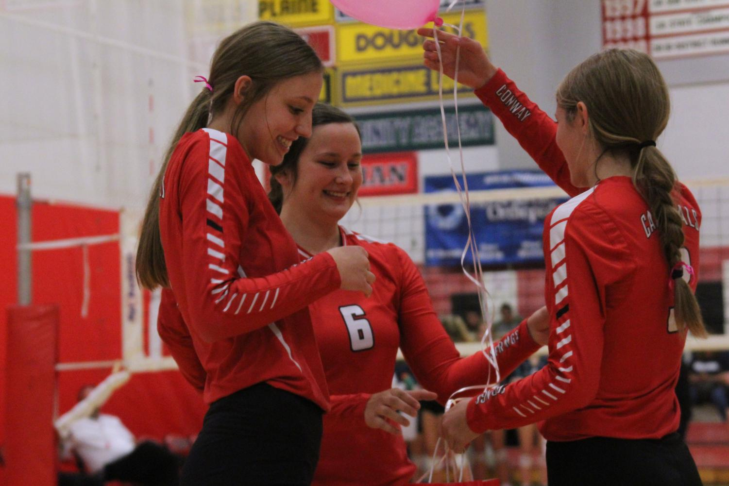 """During senior night, senior Karley Mooneyham is given a gift by junior Kyla Echelberry and sophomore Kenzie Wenke. """"I feel bittersweet because I'm pretty done with high school, but I loved volleyball and have played it for a long time,"""" Mooneyham said."""