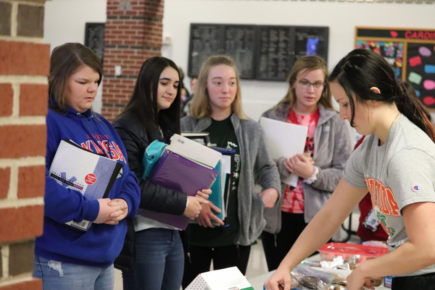 Senior Karley Mooneyham hands out treats to juniors Addie Barkley and Molly Bender, and sophomores Rosalyn Zoglmann and Abby Botkin.  All proceeds went to helping the animals and people in need.