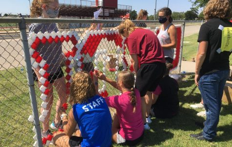 """Stuco members place colored fence cups inside the holes of the fence to form the words """"CARDINAL PRIDE."""" This took place Aug. 22, before school started as an orientation activity."""