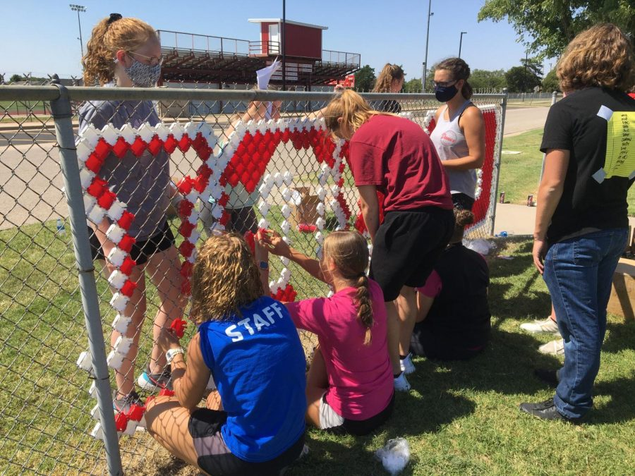 "Stuco members place colored fence cups inside the holes of the fence to form the words ""CARDINAL PRIDE."" This took place Aug. 22, before school started as an orientation activity."