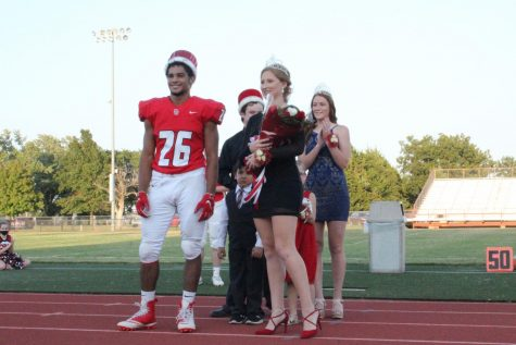 Seniors Tatum Wykes and Jonathan Wright smile as friends and family applaud for them after getting homecoming king and queen. Former king Philip Ast and queen Madison Pauly stood with kindergarteners Cooper Nichols and Avery Cox congratulating them on their win.