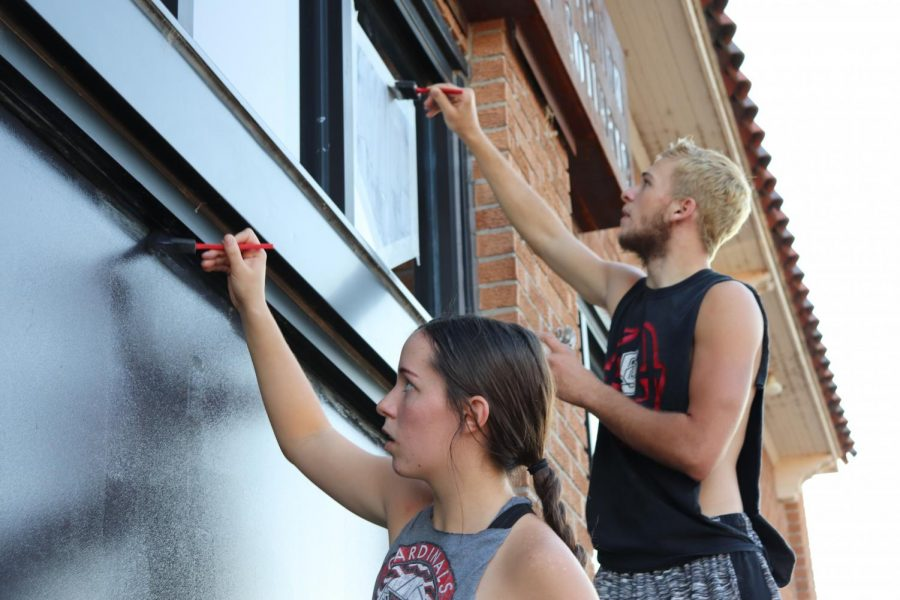 Juniors+Lauren+Mercer+and+Ian+Solomon+paint+the+ELP+Aviation+building+window+during+the+window+painting.+They+tied+with+the+sophomores+for+first+place.