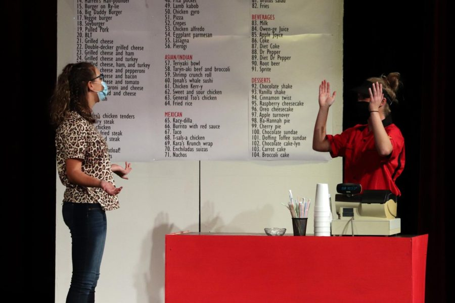 During the performance, sophomore Caitlyn May and senior Molly Bender act out an argument on stage over the cash register. The performance was on Saturday at 7 p.m. and Sunday at 4 p.m.