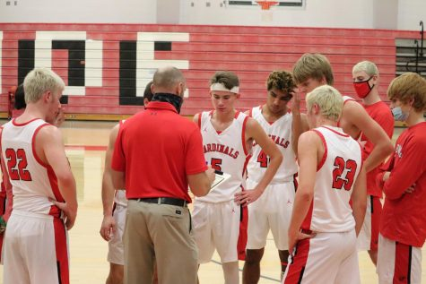 In the heat of the game, the varsity boys basketball team meet with head coach Paul Lange during a timeout to discuss their next play.
