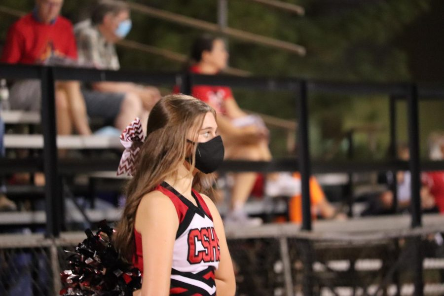 During a football game, freshman Julia Zoglmann prepares for a cheer. Due to COVID-19, the cheerleaders wear masks when not actively cheering.