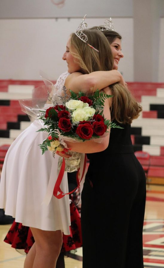 """During the ceremony, senior Lucy Boyles hugs former queen Kylie Ast. While the crowd congratulated all of the candidates. """"When I was walking down I felt calm and collected, but once they called my name I was surprised as heck,"""" Boyles said."""