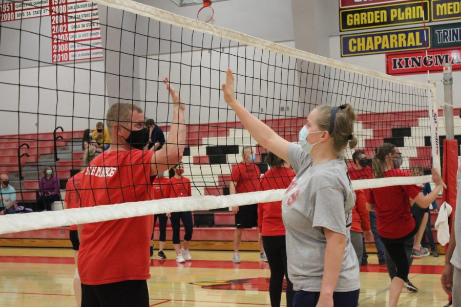 After+the+volleyball+games+were+over%2C+senior+Sadie+Schmanke+gives+her+father+and+second+grade+teacher+Keith+Schmanke+an+air+high+five+through+the+net.+This+took+place+during+the+senior+faculty+games+in+the+high+school+gym+March+30.